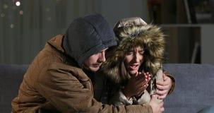 Verärgerte Paare, die zu Hause in einem kalten Winter einfrieren stock video footage