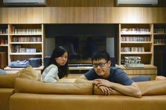 Verärgerte Paare vor Fernsehen im Wohnzimmer nachts lizenzfreies stockfoto