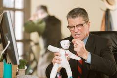 Verärgerte Professioneller, die eine Wodu-Puppe des Kollegen stößt stockfotos