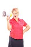 Verärgerte reife Dame, die über ein Megaphon spricht Stockbild