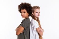 Verärgerte umgekippte Kinder, die zurück zu Rückseite mit den gekreuzten Händen stehen lizenzfreie stockfotos