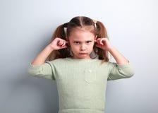 Verärgerte unglückliche Kindermädchen coverd Ohren die Finger und das gestikulieren tha Lizenzfreie Stockbilder