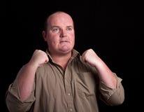 Verärgerter überladener Mann auf schwarzem Hintergrund Lizenzfreies Stockfoto