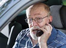 Verärgerter alter Mann, der am Handy im Auto schreit Stockfotos