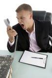 Verärgerter Angestellter, der am Telefon schreit Stockbild