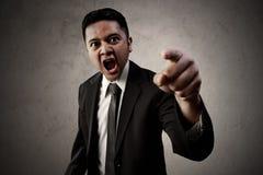 Verärgerter asiatischer Geschäftsmannpunkt Stockbild