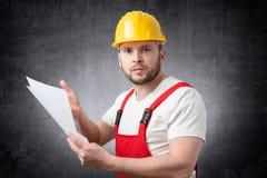 Verärgerter Bauarbeiter, der Papiere hält stockfoto