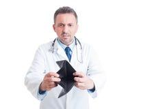 Verärgerter Doktor oder Mediziner, die leere Geldbörse zeigen Lizenzfreie Stockfotos