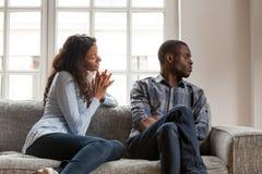 Verärgerter Ehemann und schuldige Frau, die zu Hause auf Couch sitzt lizenzfreie stockfotografie