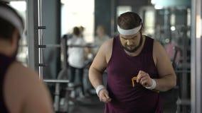 Verärgerter fetter Mann, der wegen des messenden Taillenergebnisses, Sport enttäuscht schaut stock footage