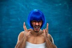 Verärgerter frustrierter junger Mann, der blaue Perücke trägt Lizenzfreies Stockfoto