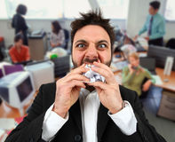 Verärgerter Geschäftsmann beim Essen des balled Papiers im Büro Stockfotos