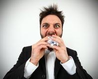 Verärgerter Geschäftsmann beim Essen von balled pape Lizenzfreie Stockbilder