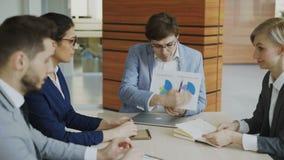 Verärgerter Geschäftsmann, der über Firmenfinanzberichte enttäuscht ist und die Angestellten sitzen am Tisch in der Sitzung gesch stock video