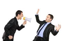 Verärgerter Geschäftsmann, der über Megaphon zu einem Mann kreischt Stockbilder