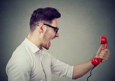 Verärgerter Geschäftsmann, der an einem roten Telefon schreit lizenzfreies stockbild
