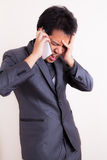 Verärgerter Geschäftsmann, der am Handy schreit Stockfoto