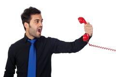 Verärgerter Geschäftsmann, der am Telefon schreit Lizenzfreie Stockfotos