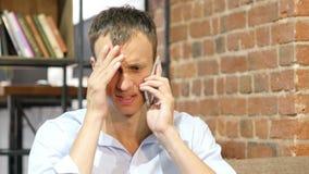 Verärgerter Geschäftsmann, der am Telefon spricht Umgekippter deprimierter Geschäftsmann