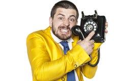 Verärgerter Geschäftsmann, der versucht, eine Telefonnummer zu wählen Stockfoto