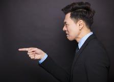Verärgerter Geschäftsmann, der vor schwarzem Hintergrund steht Lizenzfreie Stockfotografie