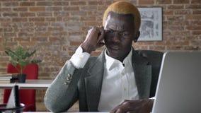 Verärgerter Geschäftsmann des jungen Afroamerikaners, der am Telefon, sitzend im modernen Büro spricht, ernst und wütend stock footage