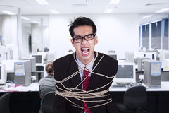 Verärgerter Geschäftsmann gebunden mit Seil im Büro stockbild