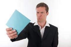Verärgerter Geschäftsmann mit einem blauen Zeichen in seiner Hand Stockbilder