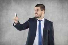 Verärgerter Geschäftsmann mit einem Telefon in seiner Hand lizenzfreies stockfoto