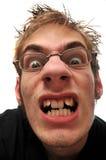 Verärgerter hässlicher Mann mit den gekrümmten Zähnen und den Gläsern Stockfotos