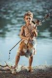 Verärgerter Höhlenbewohner, männlicher Junge mit der alten ursprünglichen Waffe, die draußen jagt Alter prähistorischer Krieger H lizenzfreies stockbild