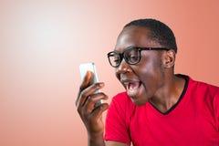 Verärgerter hübscher junger schreiender Mann während am Telefon Lizenzfreies Stockfoto