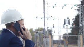 Verärgerter Ingenieur, der, sprechend am Telefon gegen einen Kraftwerkhintergrund schreit stock video footage