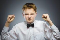 Verärgerter Junge auf grauem Hintergrund Er hob seine Fäuste zum Streik an nahaufnahme Stockbilder