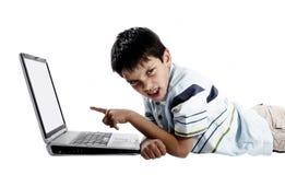 Verärgerter Junge, der einen Laptop verwendet lizenzfreie stockfotografie