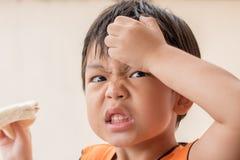 Verärgerter Junge isst Sandwichbrot Stockfotos