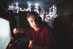 Verärgerter junger Gamer in den Kopfhörern spielt Videospiele zu Hause auf einem Computer, Blicke in die Kamera und wird ärgerlic stockbild