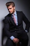 Verärgerter junger Geschäftsmann im klassischen Anzugs- und Bindungssitzen Lizenzfreies Stockfoto