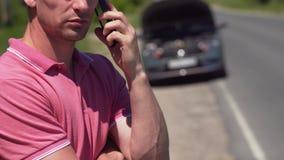 Verärgerter junger Mann, der den Notfall über Telefon nennt stock footage