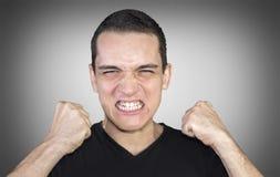 Verärgerter junger Mann, der seine Fäuste über neutralem Hintergrund zeigt Lizenzfreies Stockfoto