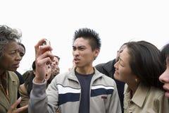 Verärgerter junger Mann, der Telefon betrachtet stockfoto