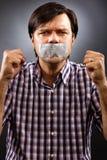 Verärgerter junger Mann mit Panzerklebeband über seinem Mund Lizenzfreie Stockfotos