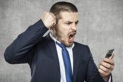 Verärgerter junger schreiender und schreiender Geschäftsmann Stockbild