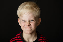 Verärgerter kleiner blonder Junge, der herauf sein Gesicht schraubt Lizenzfreies Stockfoto