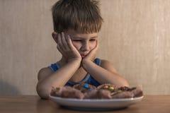 Verärgerter kleiner Junge, der am Abendtische sitzt stockfotografie