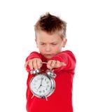Verärgerter kleiner Junge, der eine Uhr hält stockfoto