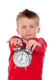 Verärgerter kleiner Junge, der eine Uhr hält stockfotografie