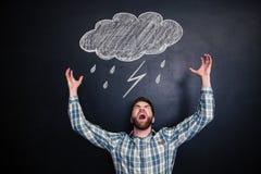 Verärgerter Mann, der über Tafel mit gezogenem raincloud steht und schreit Stockbilder
