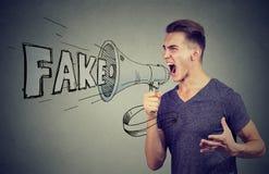 Verärgerter Mann, der in einem Megaphon verbreitet gefälschte Nachrichten schreit Lizenzfreies Stockfoto