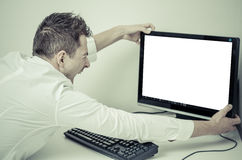 Verärgerter Mann, der seinen Computer mit einem weißen Schirm ergreift Stockfotografie